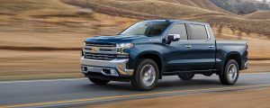 Front side view of 2021 Chevrolet Silverado 1500 driving on a road with blurred hills behind it